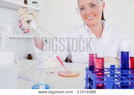 Gorgeous red-haired scientist using a pipette in a lab