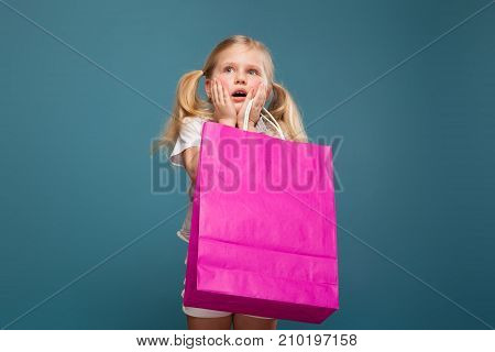Adorable Cute Little Girl In White Shirt, White Jacket And White Trousers Hold Purple Paper Bag