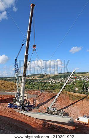 cranes lifting concrete beams for a bridge
