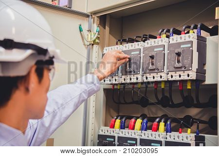 Engineer is check voltage or current by voltmeter in control panel of power plant.