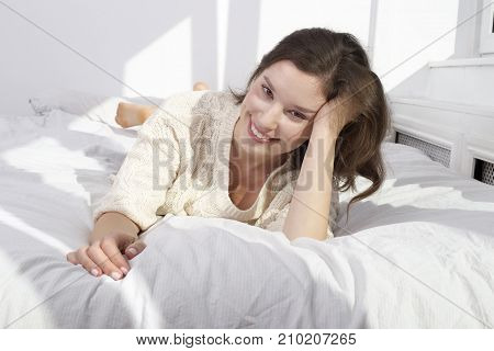 a happy young woman lying on her bed