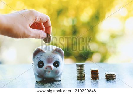 Hand saving a coin into piggy bank on blurred natural background with vintage retro color tone