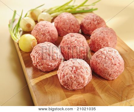 Raw delicatessen minced meat on a cutting board and vegetables. poster