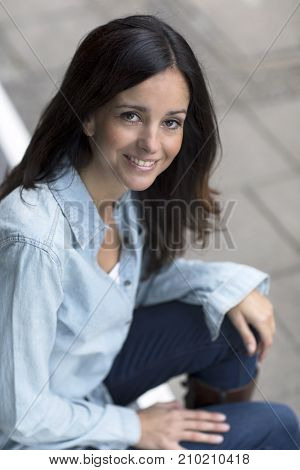 Happy young woman sitting on her doorstep