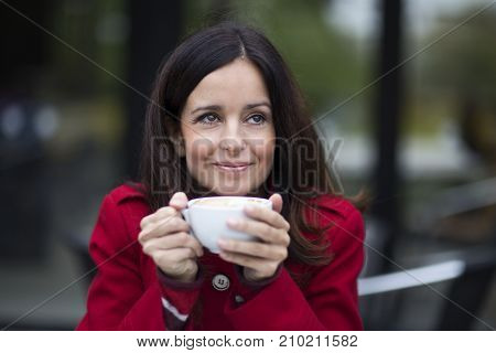 a young woman enjoying a coffee at a cafeteria