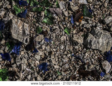 Blue and green glass pieces on the rocks. Shards of glass. Blue glass pieces. Green glass pieces. Grey grunge background.