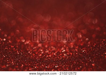 Dark red (ruby) glitter background. Sparkle texture. Abstract gradient background blurred for New Years or Christmas holiday