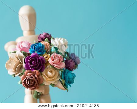 select focus of flower. The wooden puppet holds flower and standing on the wood table. the background is blue and copy space for text