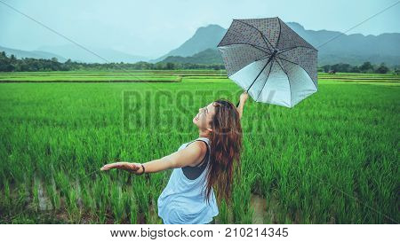 Asian women travel relax in the holiday. Women stand in rain umbrellas. On the meadow During the rainy season.Thailand