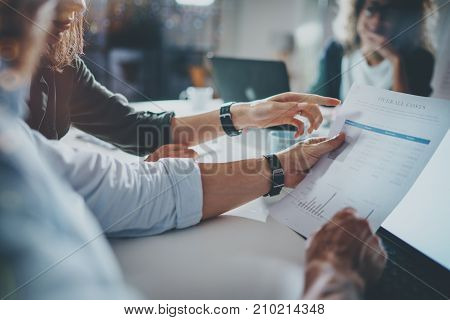 Young people making conversation with partners at the table.Man holding paper document in hand. Horizontal.Blurred background