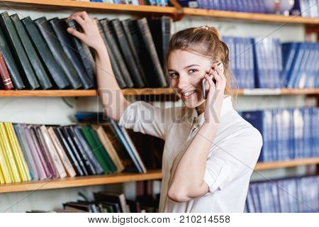 Pretty smiling student talking with phone. Beautiful girl posing on the camera and picking up book from shelves. Close-up of girl.