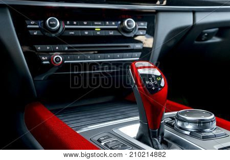 Red Automatic gear stick of a modern car. Car interior details.