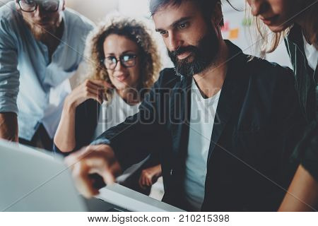 Coworkers working together in modern office.Bearded man talking with colleague and using mobile laptop while sitting at the wooden table.Horizontal.Blurred background.Cropped