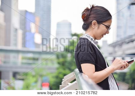 Relaxed Chinese Business Woman using smart phone on skyscraper building background in the city. Copy space.