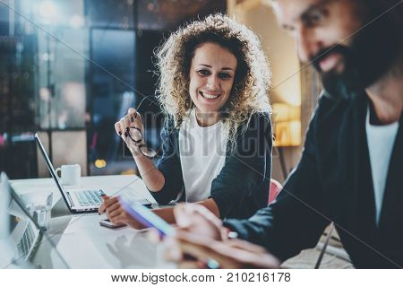 Two coworkers working process photo.Young woman working together with colleague at night modern office loft.Teamwork concept.Blurred background.Horizontal