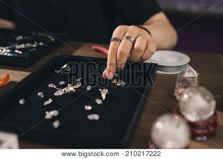 Female designer making jewelries at a jewelry shop
