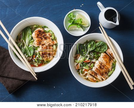 Asian style spicy udon noodle soup with fried chicken on a blue background top view