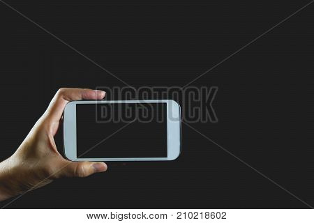 Woman hand holding smart phone isolated on dark background.