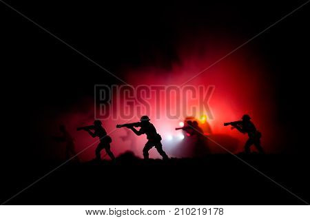 Military Silhouettes Of Soldiers Against The Backdrop Of Dark Foggy Sky. Battle Scene With Explosion