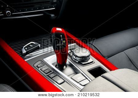 Red automatic gear stick of a modern car car interior details
