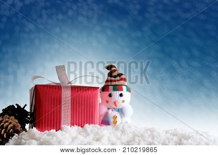 Merry christmas and happy new year background. Snowman fir and red gift boxes with winter background.