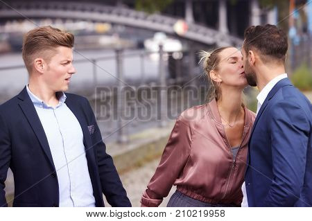woman kissing man while another is upset and watching