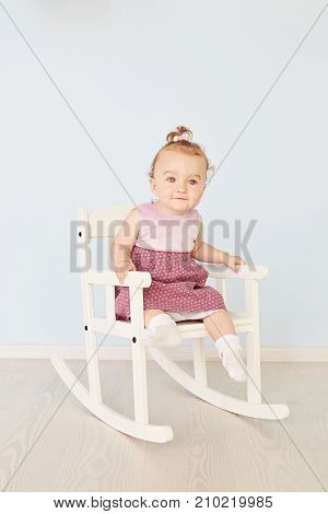 Fashionable little cute girl sitting thoughtful on the white chair posing looking away