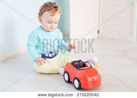 Cute little boy playing with a toy car. Happy kid sitting in studio