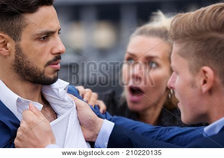 two handsome men fighting while a woman is trying to intervene