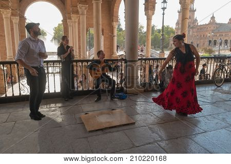 SEVILLE SPAIN - OCTOBER 01 2017: Young Spanish woman dancing Sevillanas wearing the traditional folk dress in flamenco traditional dance of Spain. Performing show in the Plaza of Spain Seville