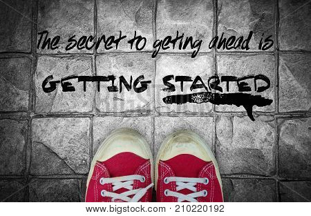 The secret togetting ahead is getting start : Quotation over pavement and red sneaker background