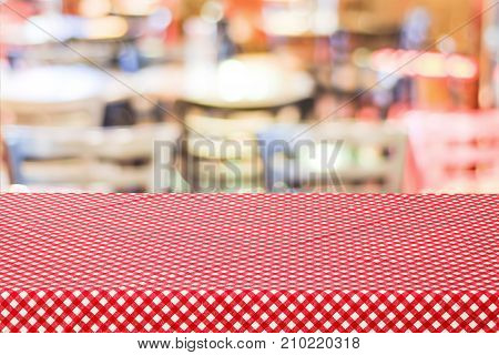 Empty table covered with red check tablecloth over blurred restaurant with bokeh light background product food display