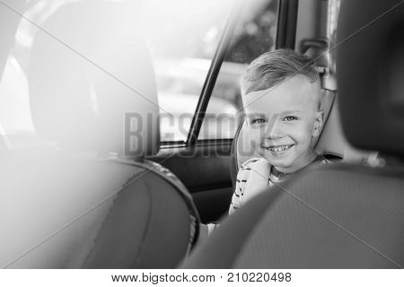 portrait happy toddler boy sitting in the car seat (Black and white)