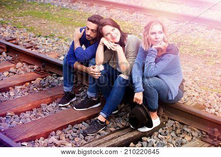 portrait of three friends sitting on train tracks and enjoying the sun