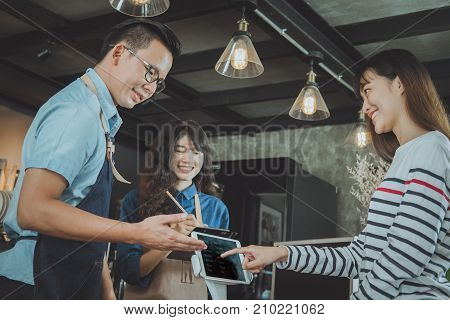 Asian baristas are recommending coffee menu to customer. Cafe restaurant service food and drink industry concept.