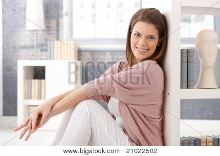 Happy Woman sitting in smart Living Room am Bücherregal, lächelnd in die Kamera.?