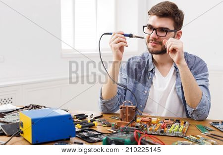 Repairman prepare for soldering computer circuit in workshop. Young engineer fixing electronic component of motherboard, copy space