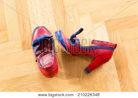 A pair of used shoes of a woman on the floor.