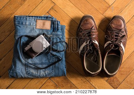 A pair of fretted blue jeans, brown shoes, and a camera lie by on the floor.