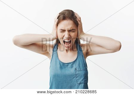 Portrait of unhappy brunette young student girl in blue shirt closing ears with hands, screaming loudly from head pain, standing with closed eyes, being pissed off loud sounds in neighbours flat