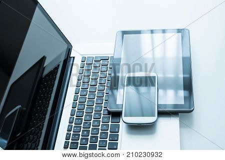 A smartphone, a laptop computer and a Tablet PC together on a desktop.