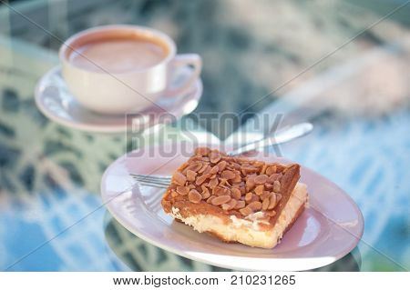 A delicious dessert: almond tart with cream, and a cup of  a hot drink on a beautiful glass table.