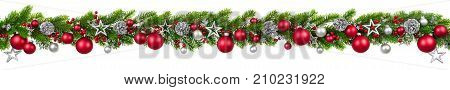 Extra wide Christmas border with hanging garland of fir branches red and silver baubles pine cones and other ornaments isolated on white