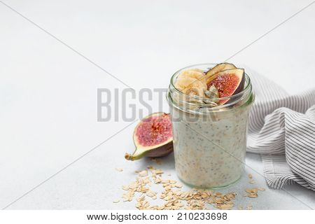 healthy diet breakfast. overnight oatmeal with chia seeds and fruits: banana figs pumpkin seeds on a light background
