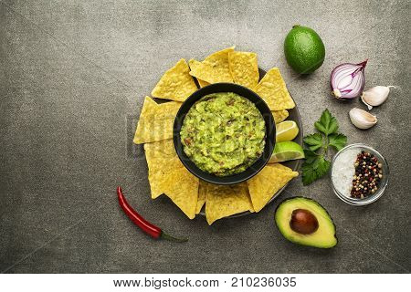 Guacamole sauce with fresh ingredients and corn nachos chips