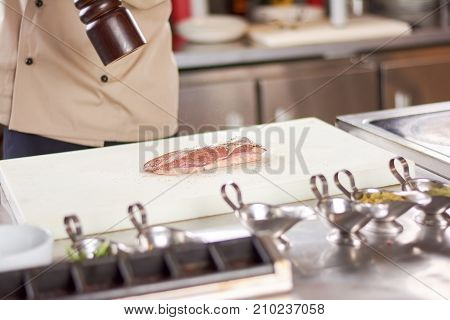 Chef processing raw meat with ground pepper. Cook sprinkling a spices on poultry breast fillet.