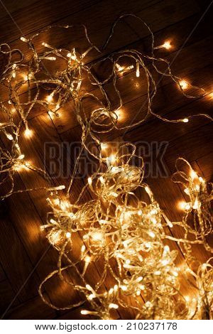 Christmas lights garland on dark background. Christmas card with copy space for greeting text.
