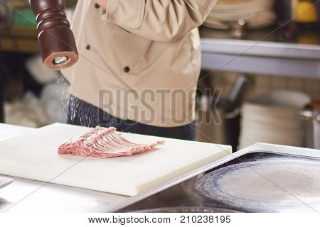 Chef sprinkling ground pepper on meat ribs. Cooking lamb ribs at restaurant kitchen by chef.