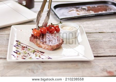 Delicious steak served with cherry tomatoes. Chef decorating ribeye steak with cherry tomatoes and sauce from madagascar pepper. Tasty steak with vegetables and sauce.