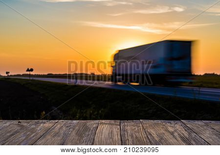 Empty Rustic Wood Table Top With Motion Blurred Truck At Sunset Background. Can Montage Or Display Y